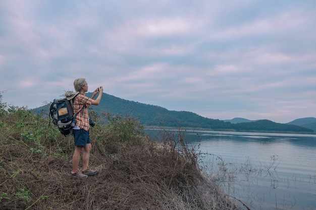 Young man trekker use smartphone take photo enjoy traveling with backpack