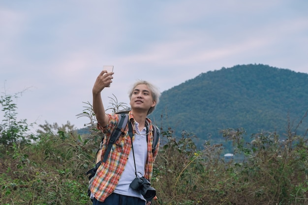 Young man trekker use smartphone take photo selfie enjoy traveling with backpack