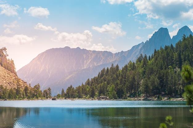 Молодой человек, идущий на вершину зеленой горы, наслаждаясь удивительными пейзажами во время заката