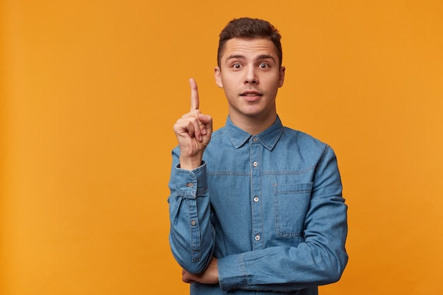 Young man in trendy denim shirt looks inspired, holds his index finger upwards looking at the front