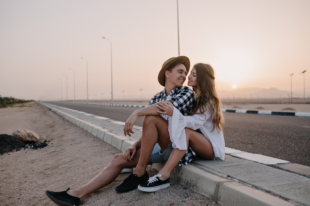 Young man in trendy hat looking with love at his graceful girlfriend in white shirt, while resting after walk. couple of travelers sitting near to road and gently embracing with sunset