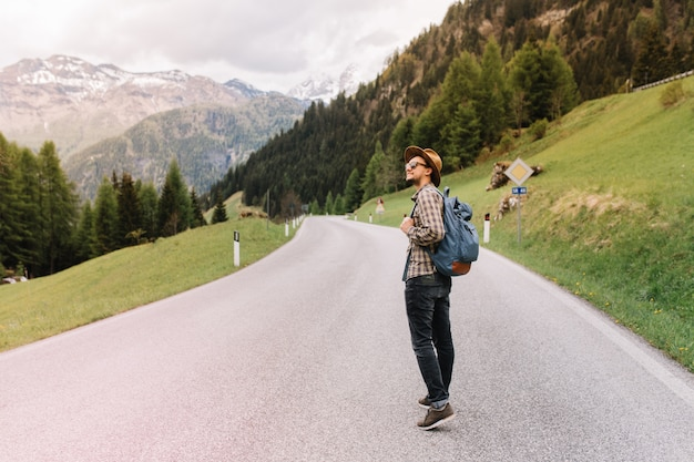 Young man in trendy hat standing in the middle of highway and looking away, enjoying fresh air near italian alps