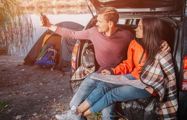 Young man tries to catch signal on his satellite phone. he looks at it and hold in hand. young woman has map on her nap. she look at phone as well. couple is serious.