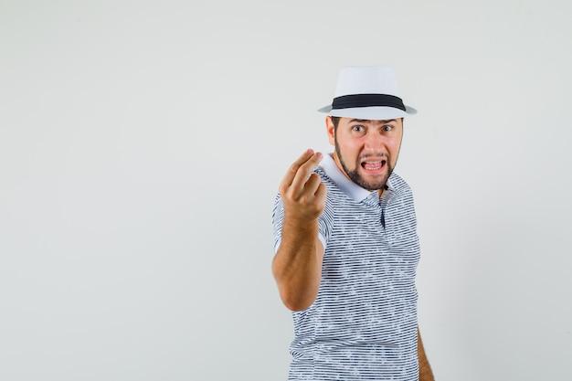 Giovane che cerca di spiegare qualcosa mentre urla in t-shirt, cappello e sembra furioso. vista frontale.