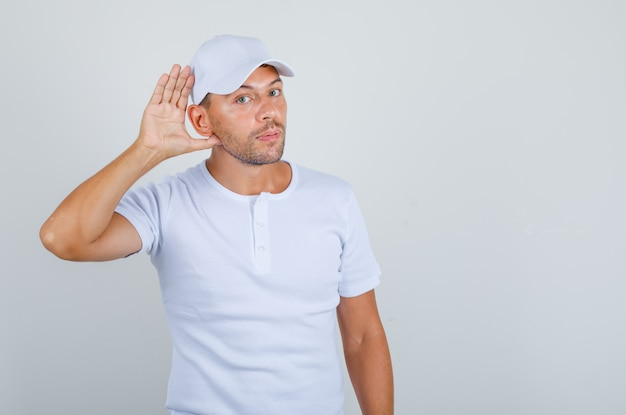 Young man trying to hear with ear gesture in white t-shirt, cap front view.