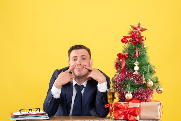 Young man trying to smile sitting at the table near xmas tree and presents on yellow