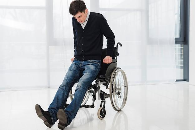 휠체어에서 얻는 것을 시도하는 젊은 남자