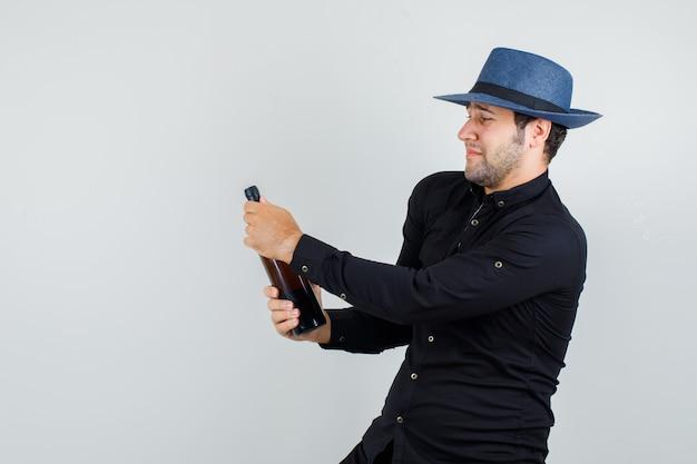 黒のシャツでアルコールボトルを開こうとしている若い男