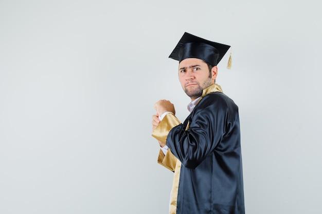 대학원 제복을 입은 알약의 병을 열려고 호기심을 찾고 젊은 남자.
