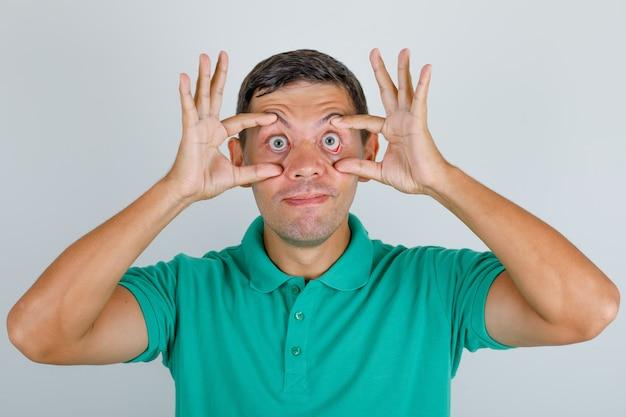 Молодой человек пытается открыть глаза пальцами в зеленой футболке и выглядит усталым, вид спереди.
