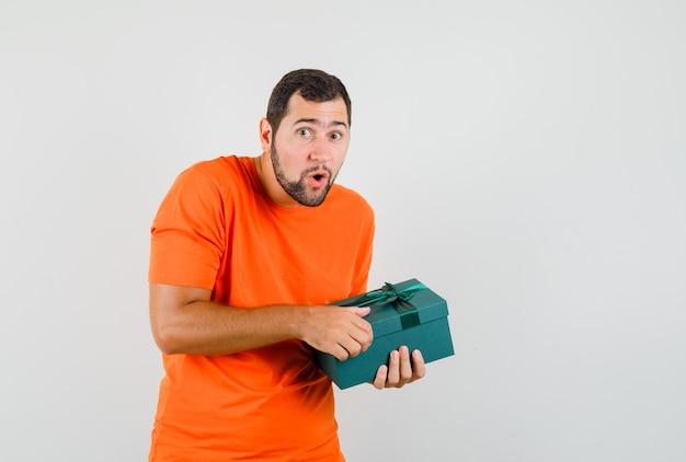 オレンジ色のtシャツでプレゼントボックスを開こうとしている若い男と好奇心旺盛に見えます。正面図。