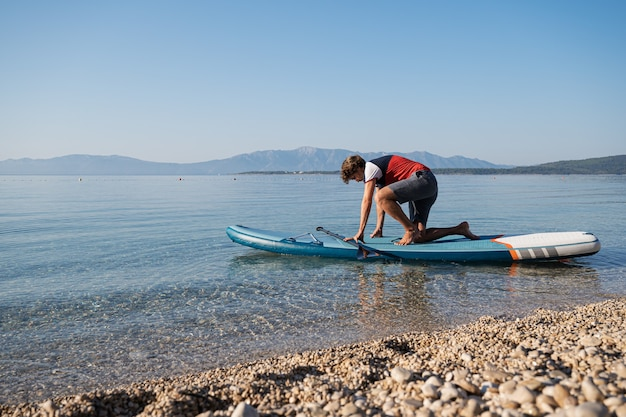Молодой человек пытается встать на доске на красивом спокойном утреннем море у галечного пляжа.