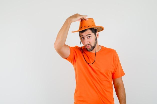 오렌지 티셔츠 전면보기에서 그의 모자를 벗고 젊은 남자.