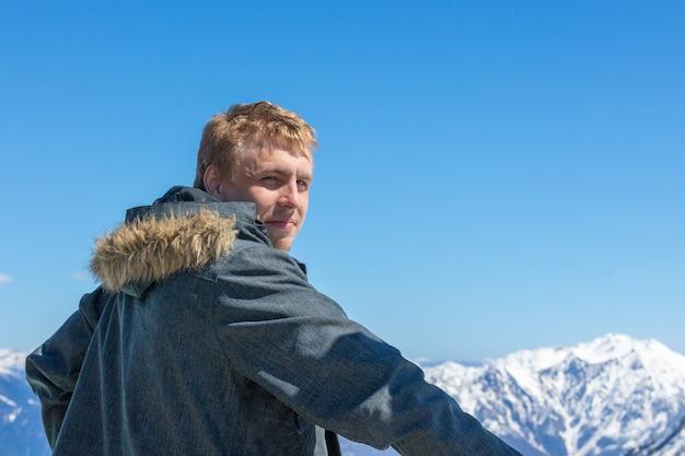 若い男が背を向けて山の風景を見た。