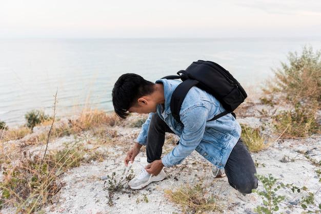 彼の靴ひもを結ぶ若い男