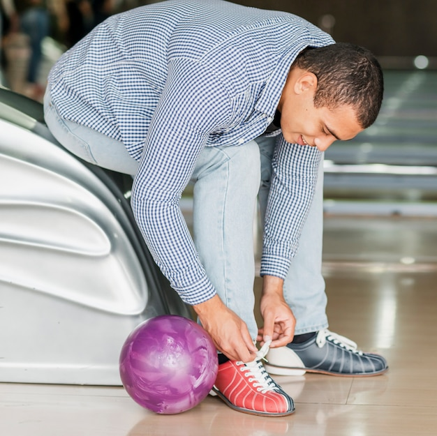 Young man tying shoelaces in a bowling club