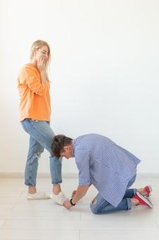 구애의 흰색 배경 개념에 포즈를 취하는 그의 사랑하는 여자의 구두 끈을 묶는 젊은 남자