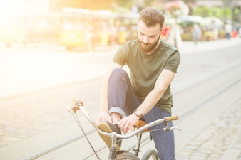 Young man tying show before riding bicycle in city