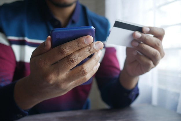 Молодой человек, набрав детали кредитной карты на смартфоне