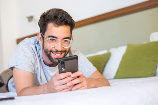 Young man typing a message in bed