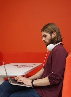 ノートパソコンに入力する若い男
