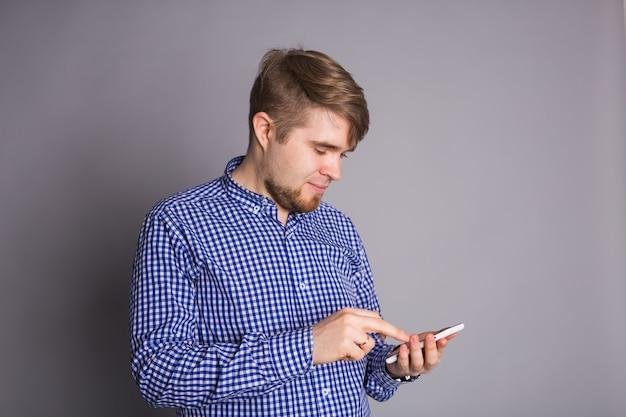 Молодой человек набирает текстовое сообщение на своем мобильном телефоне на фоне серой стены. Premium Фотографии