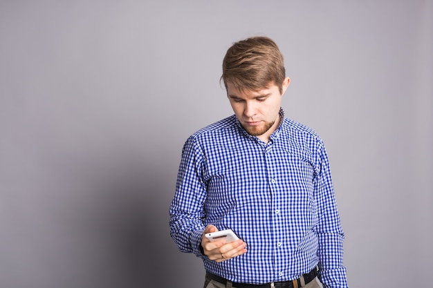 Молодой человек набирает текстовое сообщение на своем мобильном телефоне на фоне серой стены.