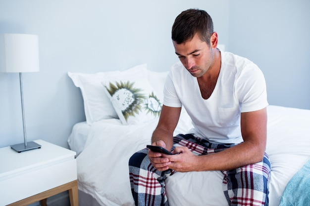 Young man typing a text message on phone