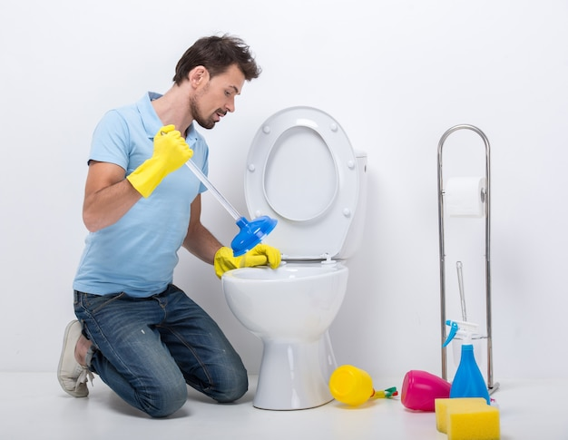 Young man unclogging a toilet with plunger.
