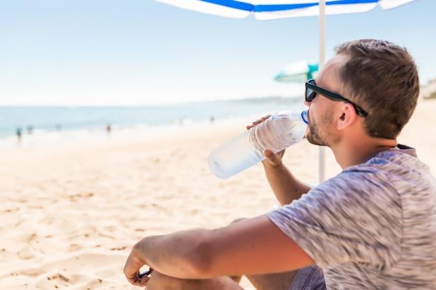 緑の太陽傘の下で若い男はビーチで水を飲む