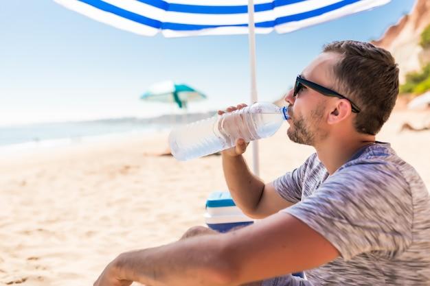 녹색 태양 우산 아래 젊은 남자가 해변에서 물을 마신다