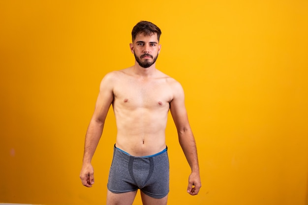 Young man in underwear facing camera