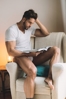 Young man in underwear reading a book