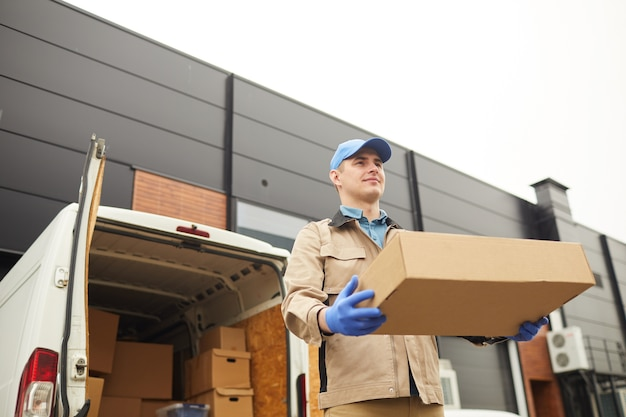 Young man in uniform carrying big cardboard box he working in cargo delivery