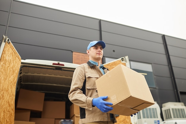 Young man in uniform carrying boxes outdoors he unloading the van