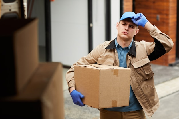 Young man in uniform carrying cardboard box to the van he loading the parcels