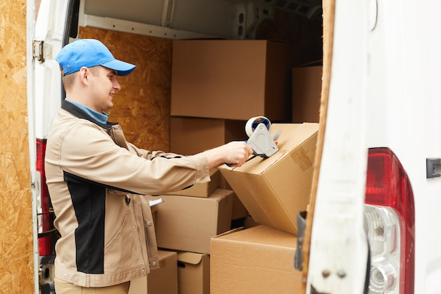 Young man in uniform packing the cardboard boxes with adhesive tape before shipping
