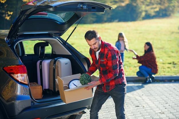 Молодой человек выгружает багаж из внедорожника, вернувшись домой из летнего семейного отдыха.