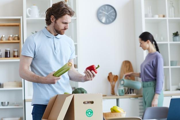 若い男が箱から新鮮な野菜を開梱し、女性がキッチンに立っている