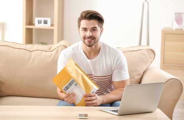 自宅で小包を開梱する若い男
