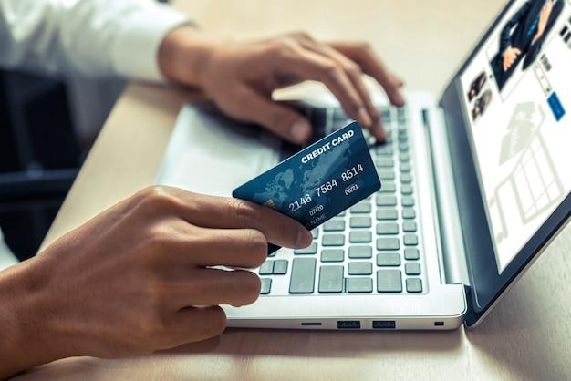 若い男はオンラインショッピングにクレジットカードを使用します