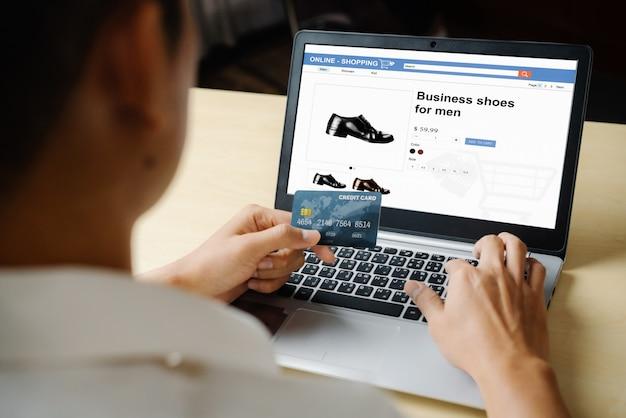 若い男がオンラインショッピングにクレジットカードを使用します