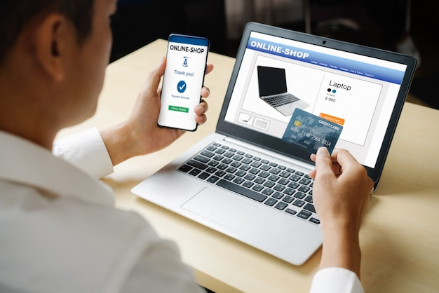 Молодой человек использует кредитную карту для покупок в интернете