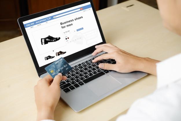 젊은 남자는 노트북 컴퓨터 응용 프로그램 또는 웹 사이트에서 온라인 결제를 위해 신용 카드를 사용합니다. 전자 상거래 및 온라인 쇼핑 개념.