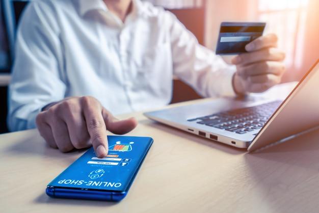 若い男は、ラップトップコンピュータアプリケーションまたはウェブサイトでオンラインショッピングの支払いにクレジットカードを使用します。 eコマースとオンラインショッピングのコンセプト。