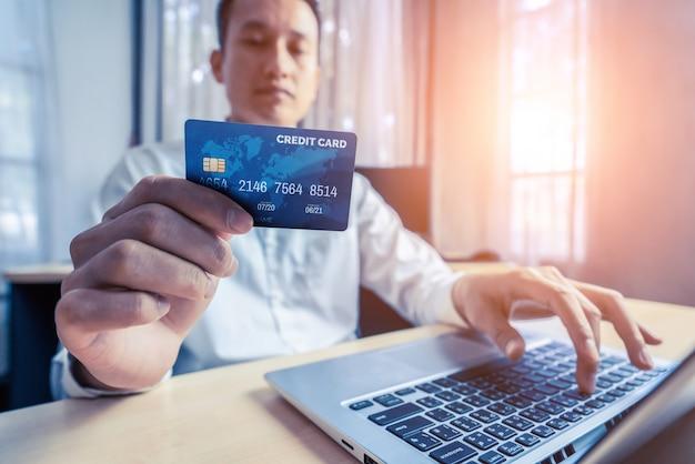 若い男は、ラップトップコンピュータアプリケーションまたはウェブサイトでオンラインショッピングの支払いにクレジットカードを使用します