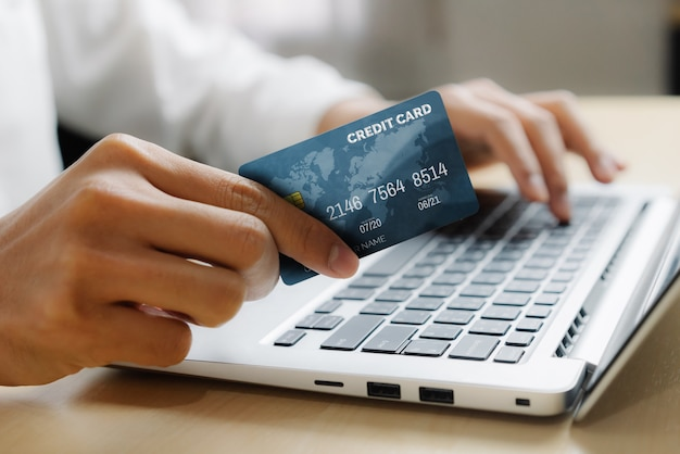 Young man use credit card for shopping payment online on laptop computer application or website. e-commerce and online shopping concept.