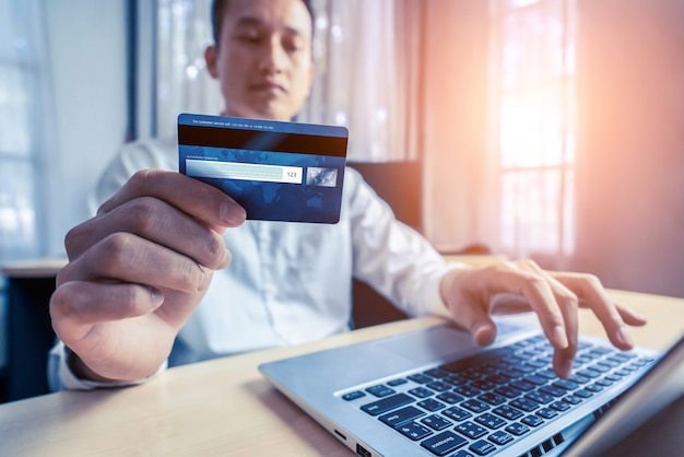 Young man use credit card for shopping payment online on laptop computer application or website