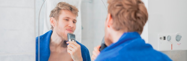 Young man use electric trimmer shave opposite the mirror