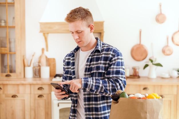 若い男はテーブルの上の新鮮な野菜とスカンジナビアのキッチンバッグでスマートフォンを使用しますオンライン
